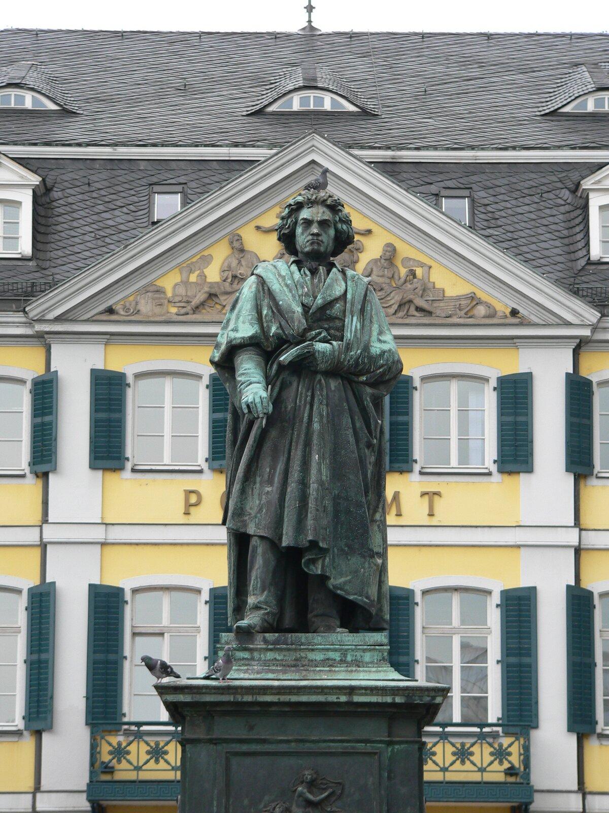 Ilustracja przedstawia pomnik Ludviga van Beethovena. Mężczyzna wśrednim wieku, ubrany wszaty dostosowane do epoki. Włosy dłuższe, lekko kręcone.