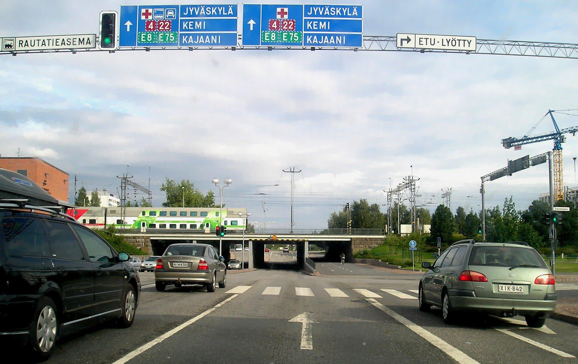 Trzypasmowa ulica, wiadukt kolejowy, pociąg. Białe napisy wjęzyku fińskim na niebieskich drogowskazach.