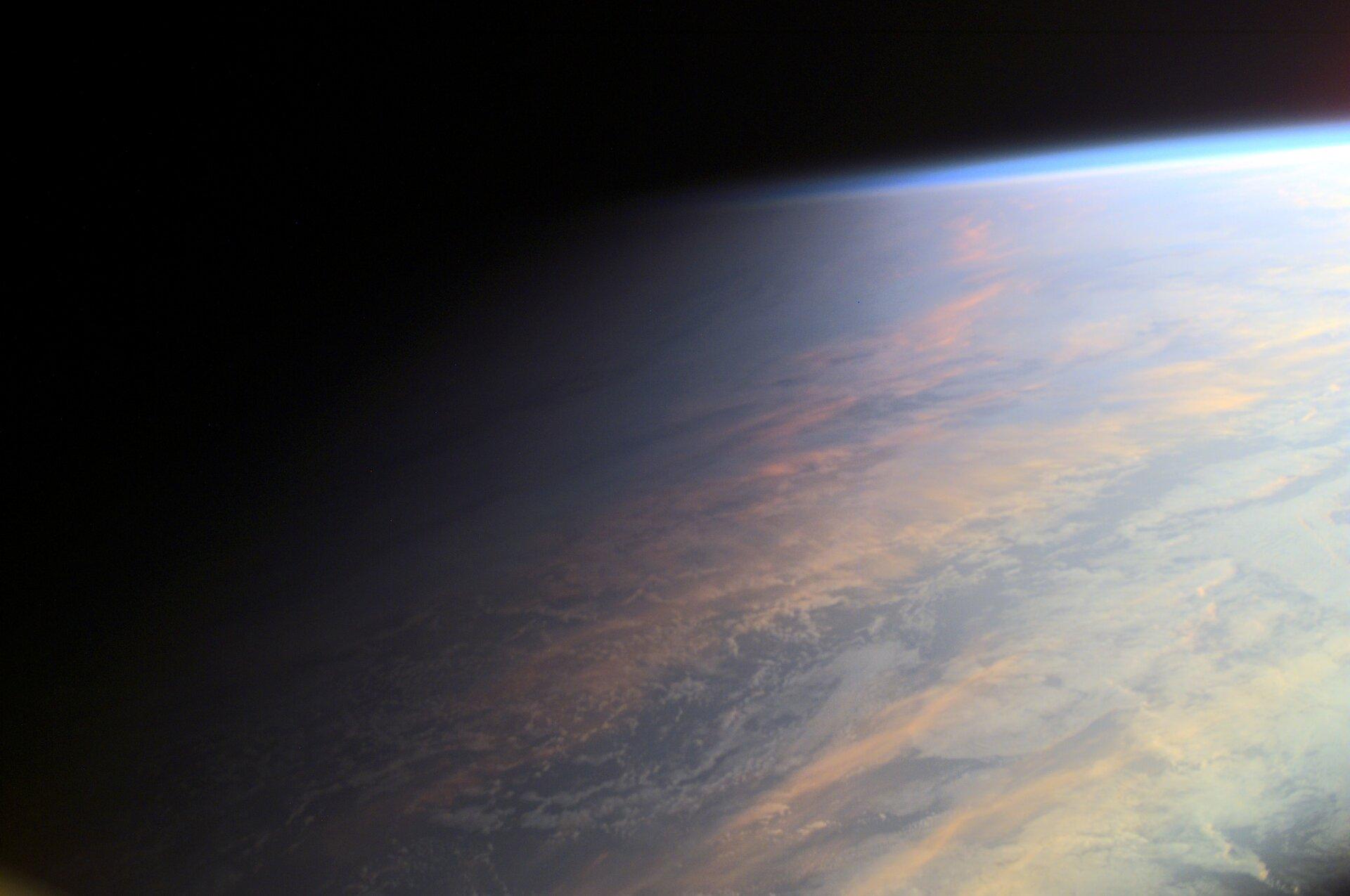 Fotografia prezentuje powierzchnię Ziemi widzianą zkosmosu. Prawa strona fotografii jest oświetlona, natomiast lewa strona.