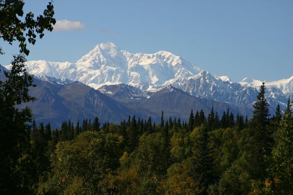 Na zdjęciu masyw górski pokryty śniegiem. Wdolnych partiach nieośnieżony, na pierwszym planie lasy.