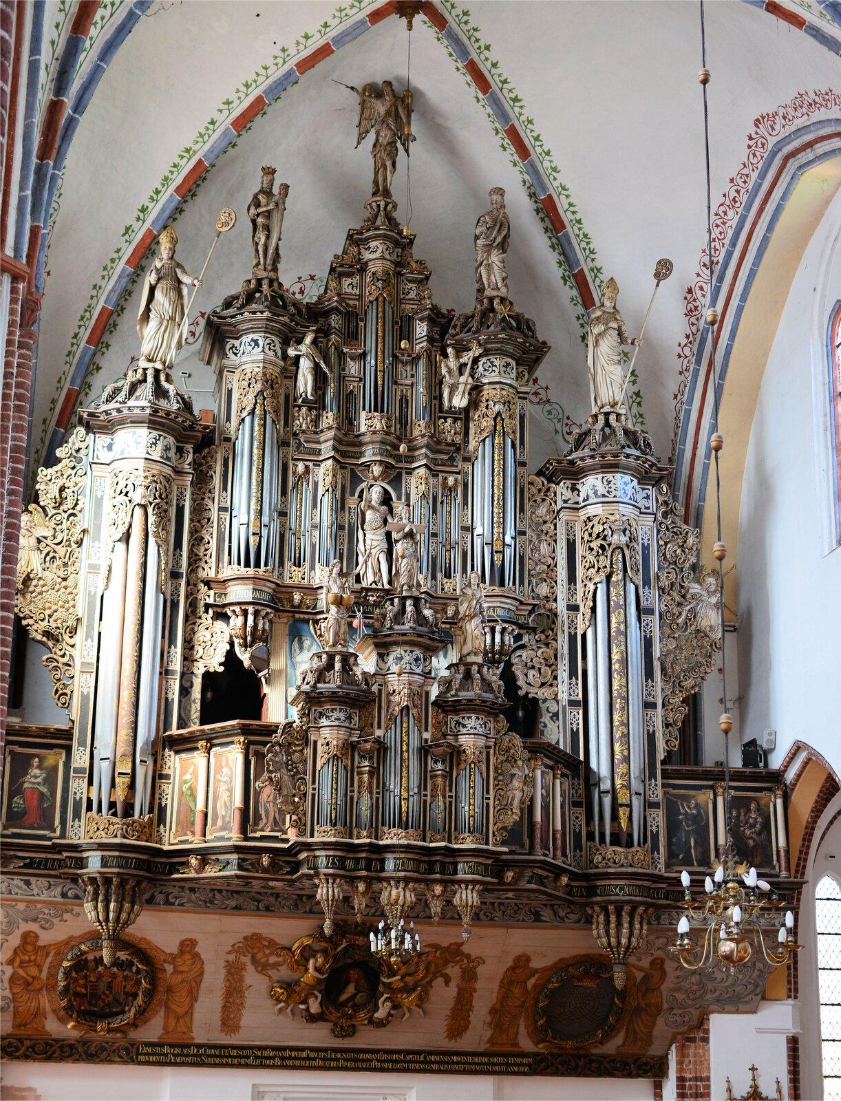 Na zdjęciu prospekt organów wKamieniu Pomorskim. Barokowy prospekt ma liczne zdobienia, jest bogato złocony, ozdobiony rzeźbami postaci biblijnych.