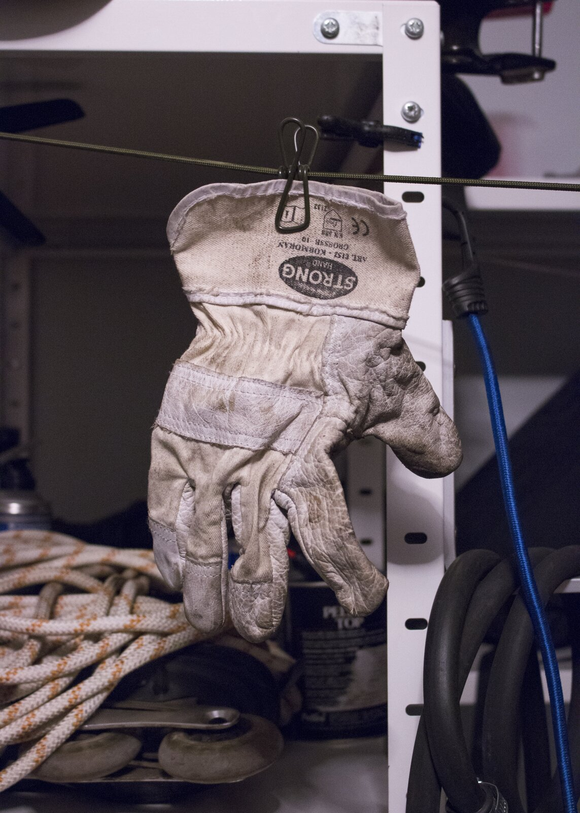 """Ilustracja przedstawia fotografię """"Rękawiczka"""". Na zdjęciu ukazana jest podniszczona rękawica robocza zawieszona na zielonej linie. Wtle znajduje się fragment regału zpółkami na których leżą liny, puszki, wąż gumowy, niebieski kabel oraz metalowe narzędzia."""