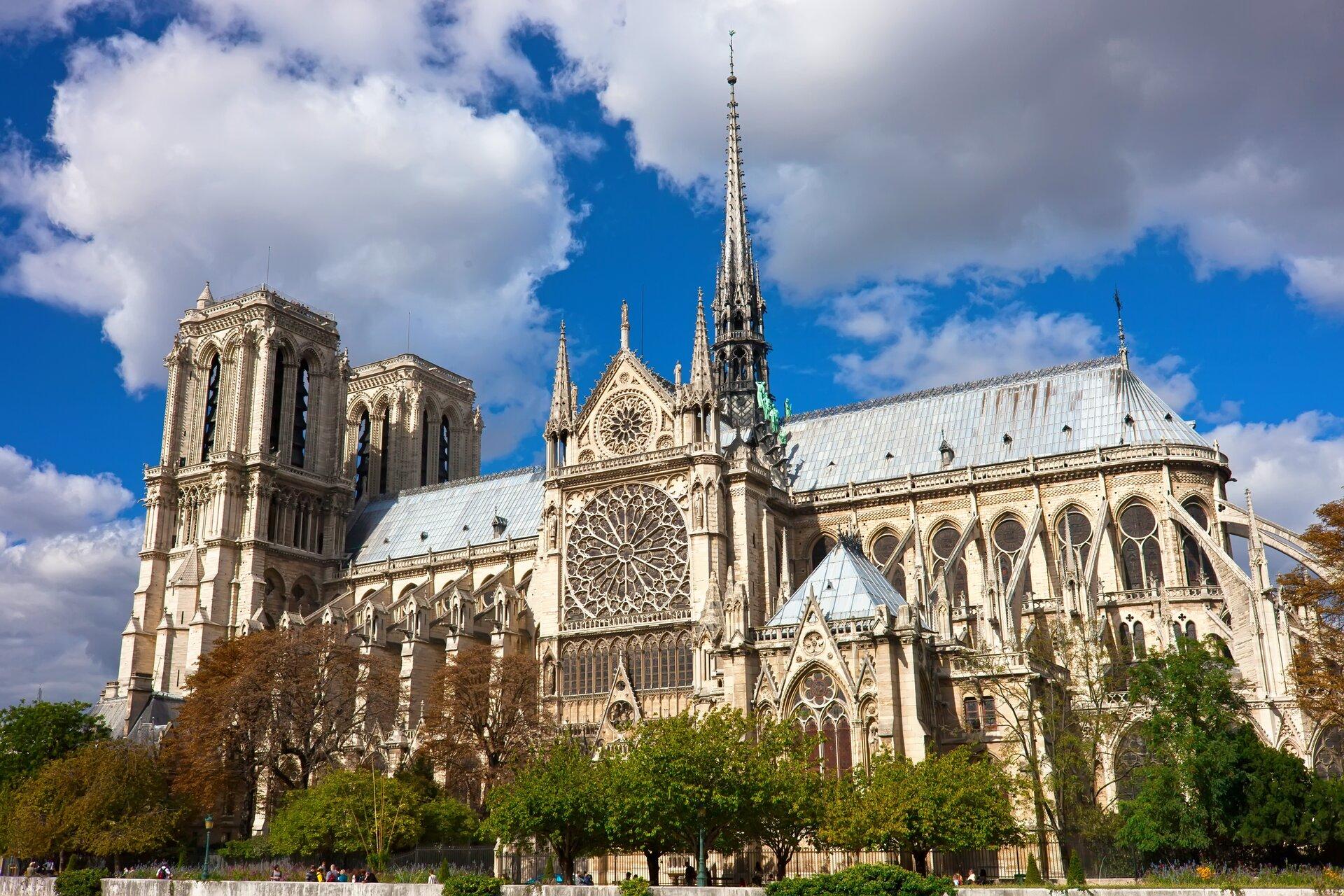 Ilustracja przedstawia Katedrę Notre-Dame wParyżu. Budowla jest strzelista, monumentalna. Na zdjęciu jest boczna część katedry zwieżą iwejściem. Centralnym punktem jest wielka rozeta, anad nią druga mniejsza. Ta część budynku zakończona jest dwiema małymi szpiczastymi wieżyczkami, awtylnej jej części widać dużą szpiczastą wieżę ijasne błękitne niebo pokryte białymi chmurami. Po lewej stronie katedy widać dwie główne kwadratowe wieże, które wgórnej części mają po dwa długie otwory okienne - biforium.