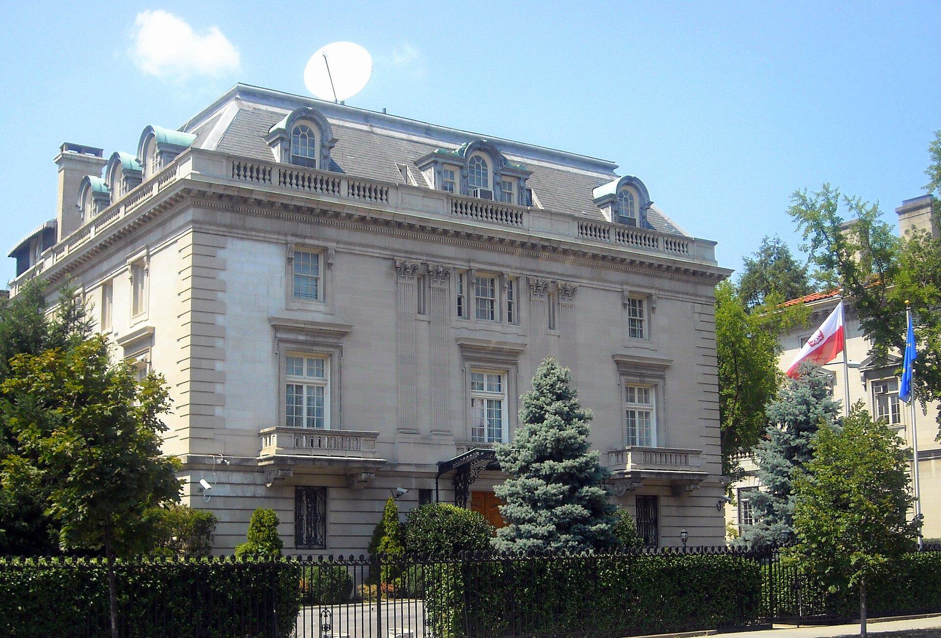 Kolorowe zdjęcie przedstawia piętrowy budynek ambasady Polski wWaszyngtonie. Budynek zbiałego kamienia. Na pierwszym piętrze duże okna. Przed oknami balustrady balkonów. Na pierwszym piętrze małe okna ozdobione rzeźbami powyżej. Wokół dachu balustrada zkamienia. Wdachu okna wformie wykuszy. Okna zaokrąglone wgórnej części. Dach pokryty szarą dachówką. Na dachu duża antena satelitarna. Przed budynkiem drzewa ikrzewy. Budynek otoczony czarnym kutym płotem. Wzdłuż płotu, od podwórza, zielony żywopłot. Po prawej stronie, przed budynkiem, dwa maszty zflagami. Po lewej flaga Polski. Na fladze godło Polski. Po prawej flaga Unii Europejskiej.