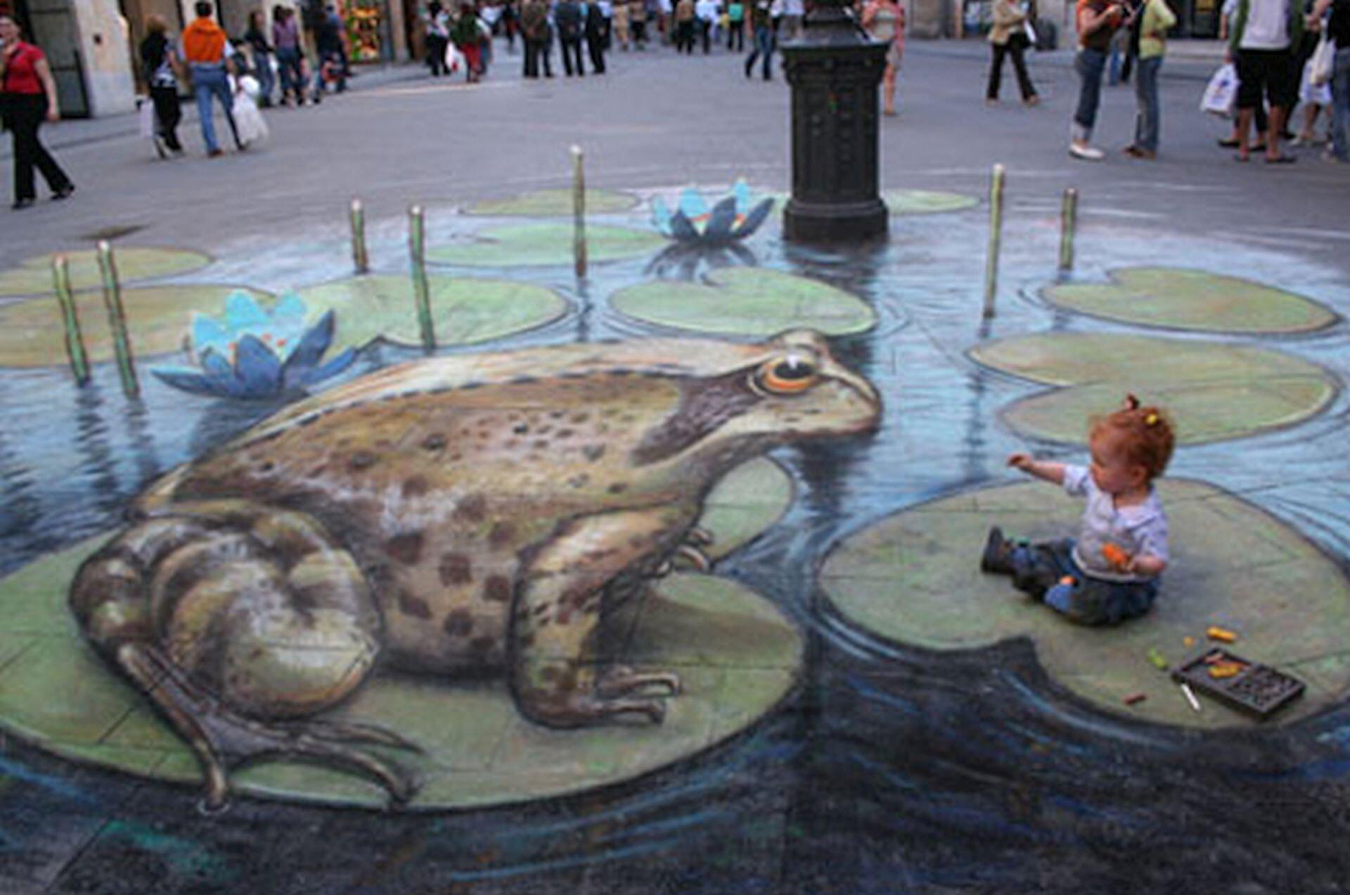 Ilustracja interaktywna przedstawia graffiti 3D Juliana Beevera na chodniku. Zdjęcie przedstawia graffiti żaby na liściach lilii wodnej. Cała grafika sprawia złudzenie trójwymiarowości. Na jednym zliści siedzi mała dziewczynka. Wtle placu chodzą ludzie.