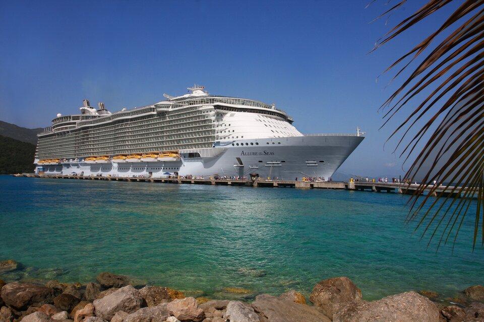 Na zdjęciu bardzo dużych rozmiarów biały statek pasażerski na morzu. Ma kilkanaście pokładów. Po bokach na burcie kilka łodzi ratunkowych.