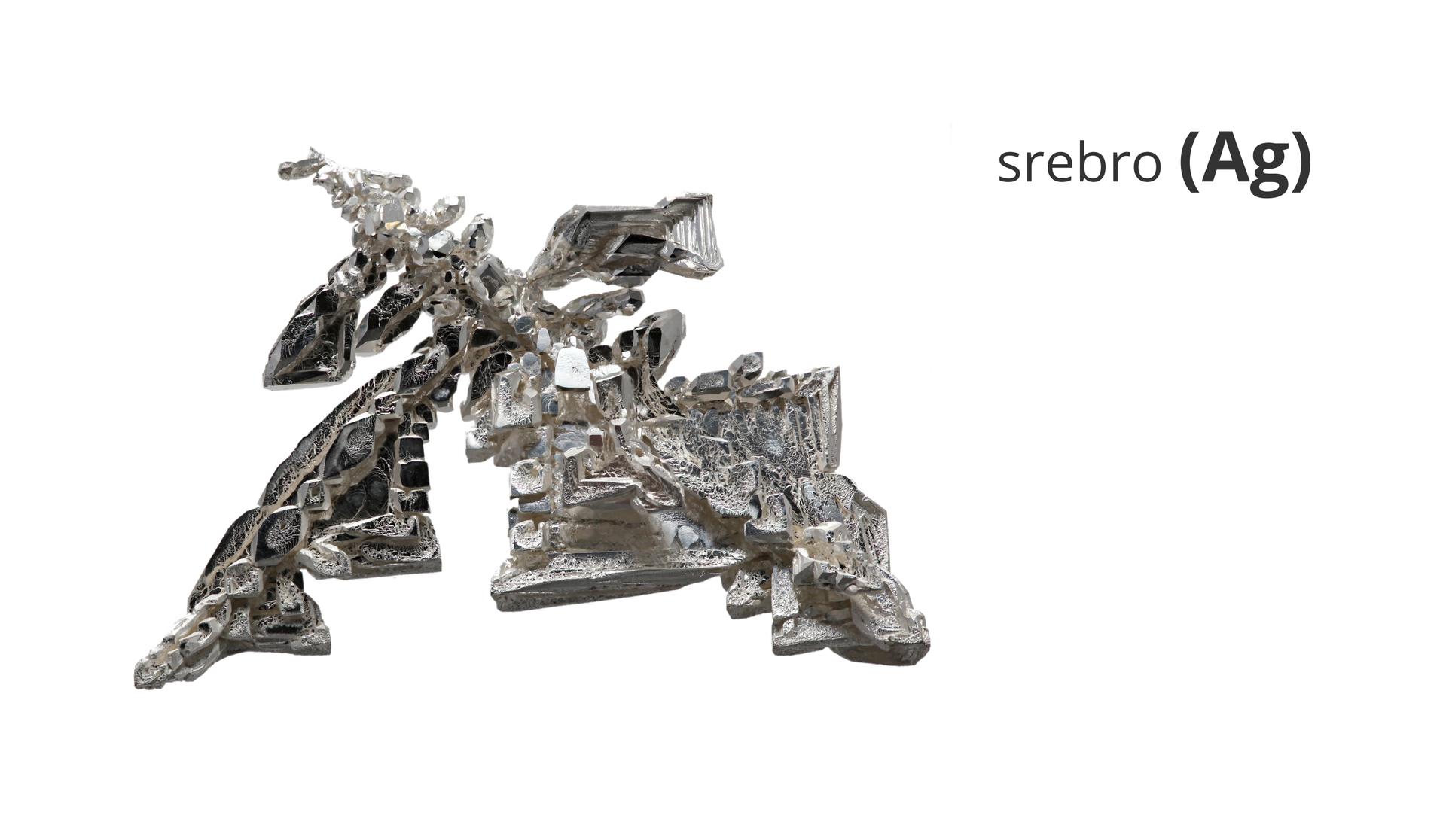 Zdjęcie przedstawia krystaliczne srebro. Obok widnieje napis srebro ijego symbol Ag.
