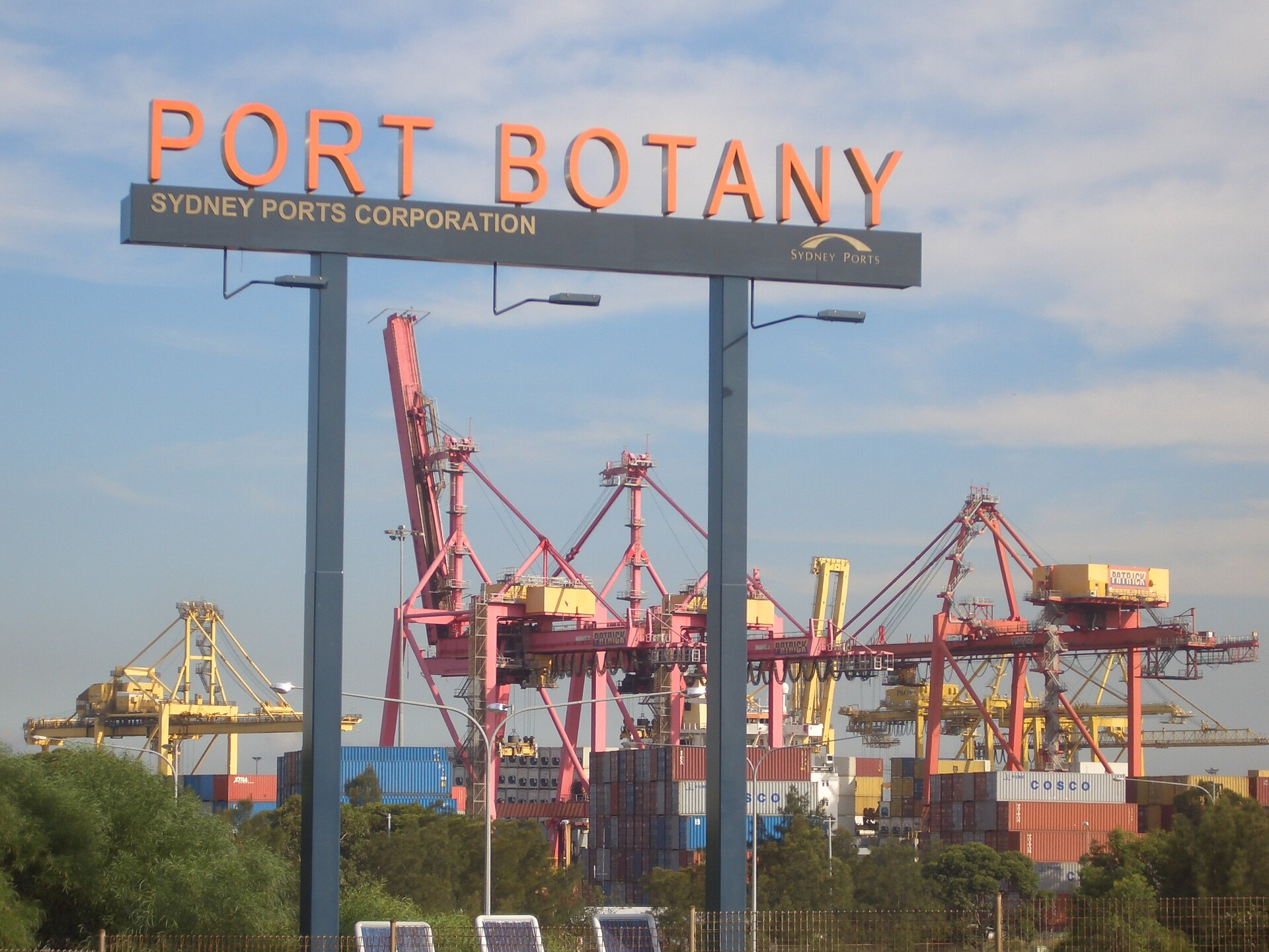 Na zdjęciu zabudowania portowe, kontenery. Na wysokich słupach szyld znapisem Port Botany.