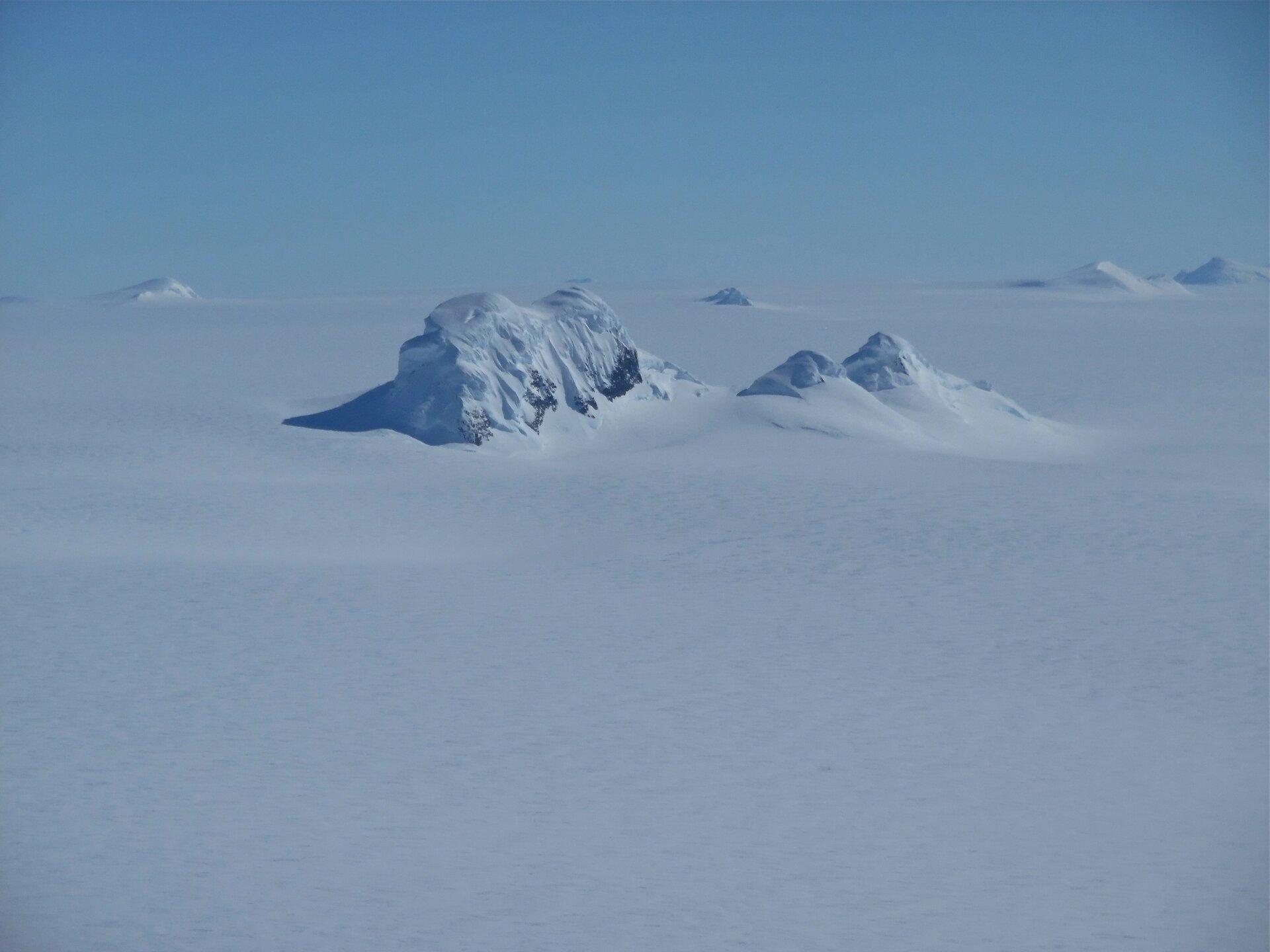 Na zdjęciu ośnieżone skaliste szczyty wystające ponad powierzchnię lądolodu.
