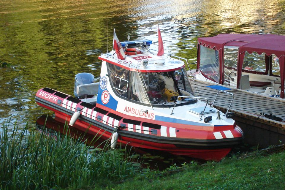 Drugie zdjęcie na prawo to mała łódź ratunkowa WOPR. Łódź przycumowana do brzegu. Kabina kapitana oszklona. Za kabiną dwa miejsca siedzące. Na dachu kabiny dwie biało-czerwone flagi.