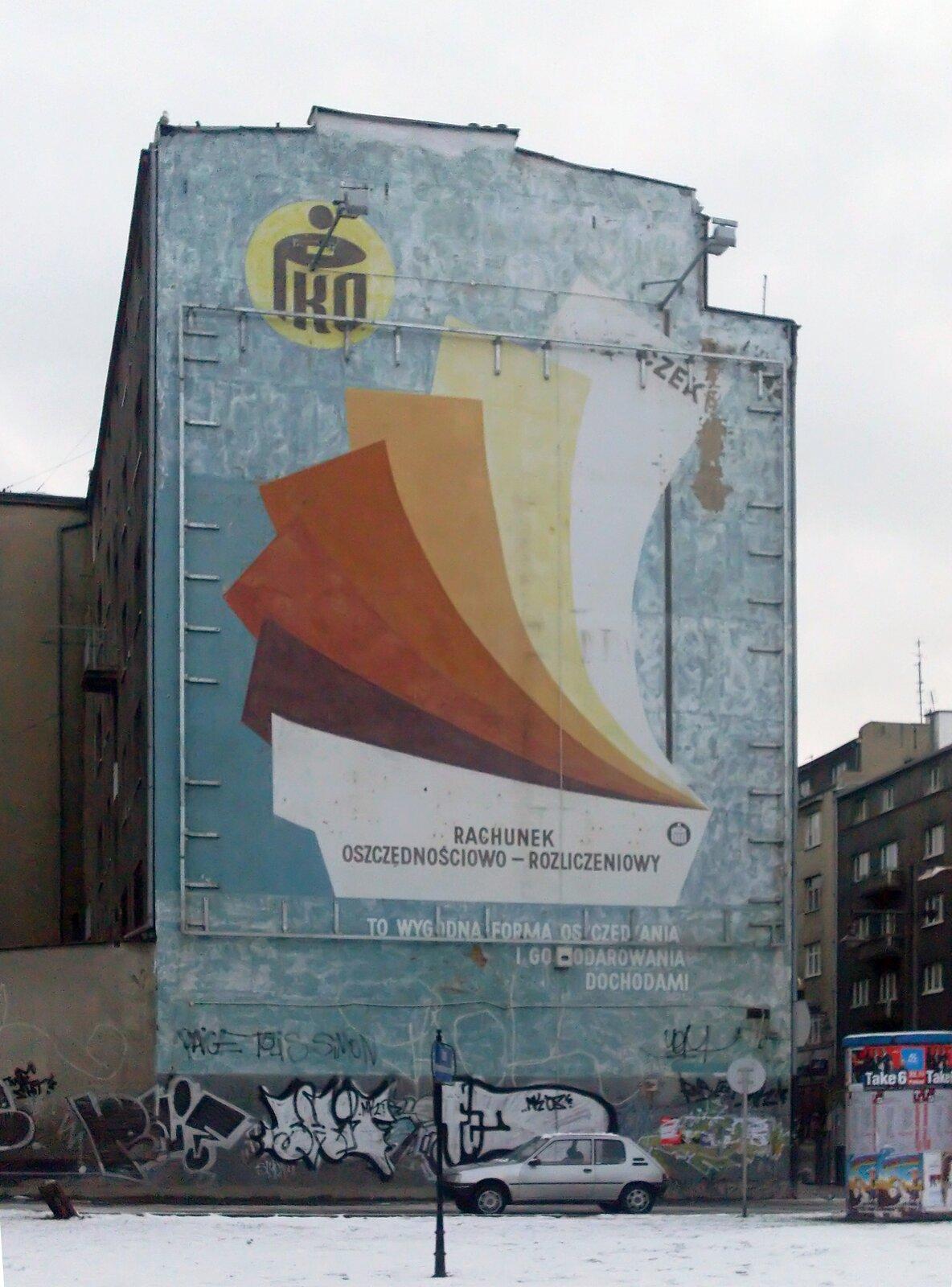"""Zdjęcie przedstawia mural, stanowiący dawną reklamę banku PKO. Na budynku widnieje napis """"Rachunek oszczędnościowo-rozliczeniowy"""", nad którym ułożone są druki. Wgórnej części, po lewej stronie znajduje się logo banku: napis PKO na tle żółtego koła. Wdolnej części budynku zamieszczone są inne, czarno-białe graffiti."""