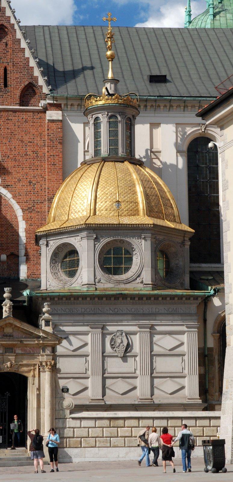 Przed wejściem do kaplicy stoją ludzie. Budynek jest zszarego kamienia, ana szczycie jest złota kopuła zwieńczona koroną ikrzyżem. Pod kopułą są okrągłe okna.