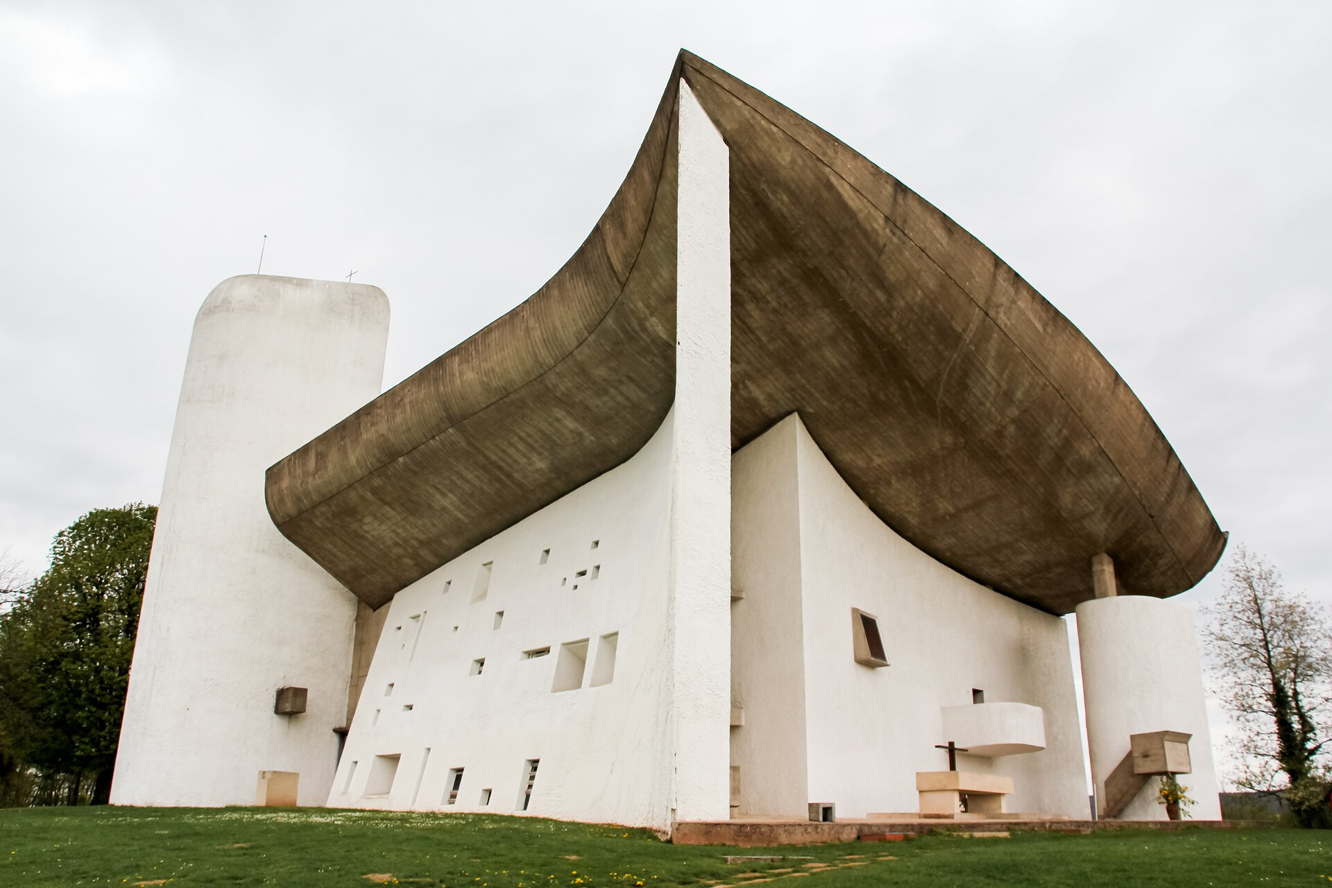 Ilustracja przedstawia kaplicę Notre Dame du Haut wokolicach Ronchamp.