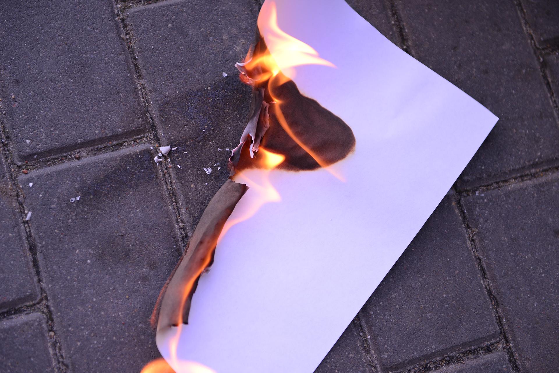 Zdjęcie przedstawia płonącą czystą kartkę papieru leżącą na chodniku.