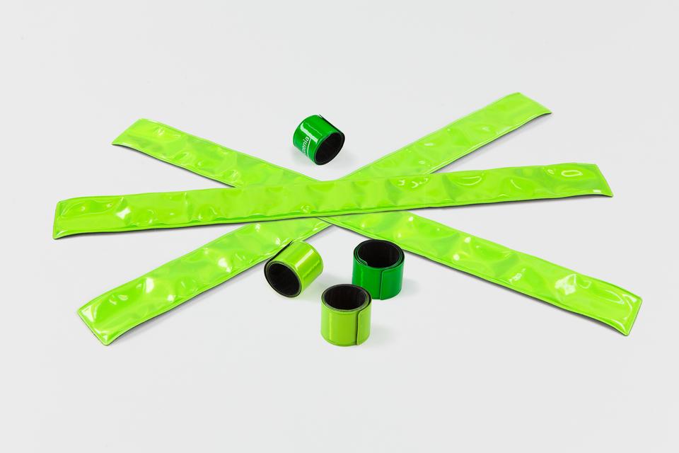 Galeria zawierająca zdjęcia przyborów odblaskowych poprawiających widoczność człowieka na drodze. Zdjęcie numer trzy przedstawia elastyczne odblaskowe zielone opaski do założenia wokół nadgarstków. Szerokość opaski to około 2 centymetry. Na zdjęciu opaski znajdują się zarówno wpostaci zwiniętej jak irozwiniętej.
