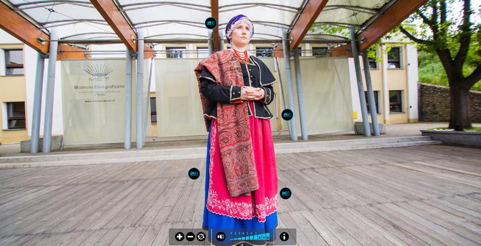 Prezentacja prezentuje odświętny strój ludowy – na przykładzie damskiego stroju kujawskiego z2 połowy XIX wieku. Strój pochodzi ze zbiorów Muzeum Etnograficznego wToruniu. Prezentacja opatrzona jest następującymi opisami: 1. Elementy stroju: ciemna wełniana spódnica, fartuch ozdobiony haftem, kabatek zpeleryną, biała koszula zhaftowanym, dopinanym kołnierzykiem, biały, haftowany czepiec, tzw. kopka, zrolowana jedwabna chustka, tzw. kaczorówka, duża wełniana chusta, tzw. mazanicha, sznur korali. 2. Charakterystycznym elementem stroju są kwieciste motywy na czepku, jest to tzw. haft kujawski. 3. Typowe obuwie jest wykonane zczarnej skóry. 4. Charakterystyczny biały motyw na fartuchu - motyw kwiatowy zawsze był biały. Same fartuchy były wykonane najczęściej zpłótna, jedwabiu iatłasu.