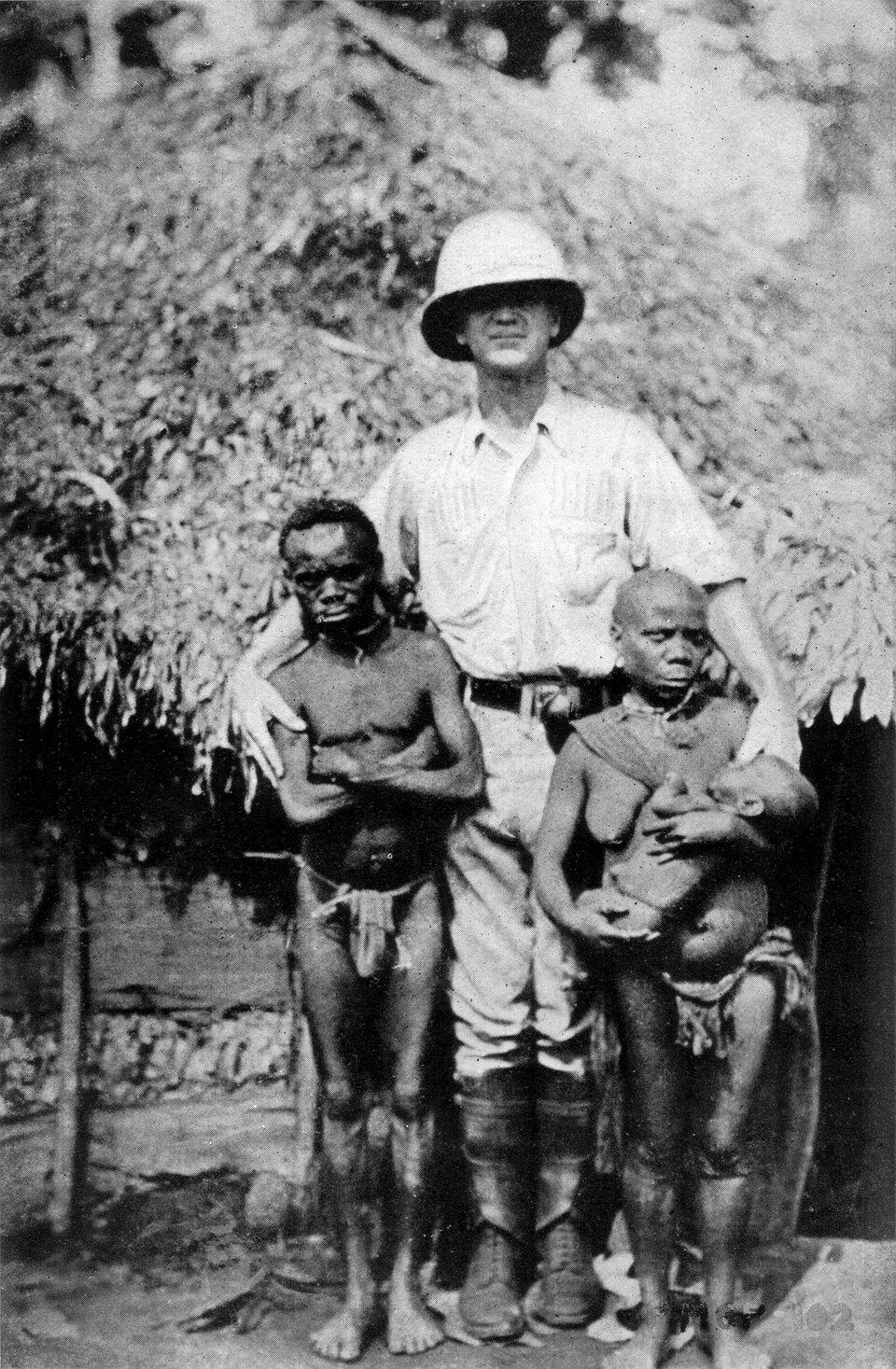 Na zdjęciu wysoki człowiek rasy białej, obok Pigmeje, znacznie niżsi. Kobieta sięga mu do łokcia, amężczyzna do ramienia.