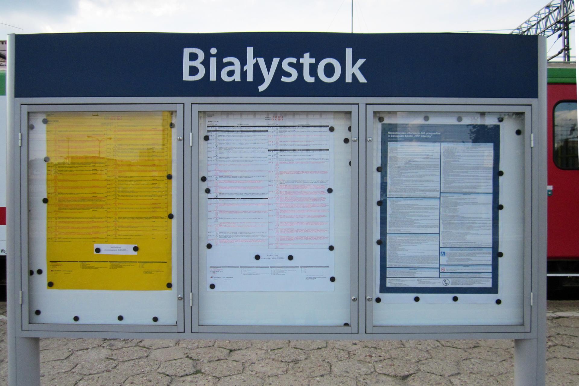 Fotografia przedstawia kolejowe rozkłady jazdy, umieszczone wprzeszklonych gablotach, ustawionych na peronie, na dworcu kolejowym.