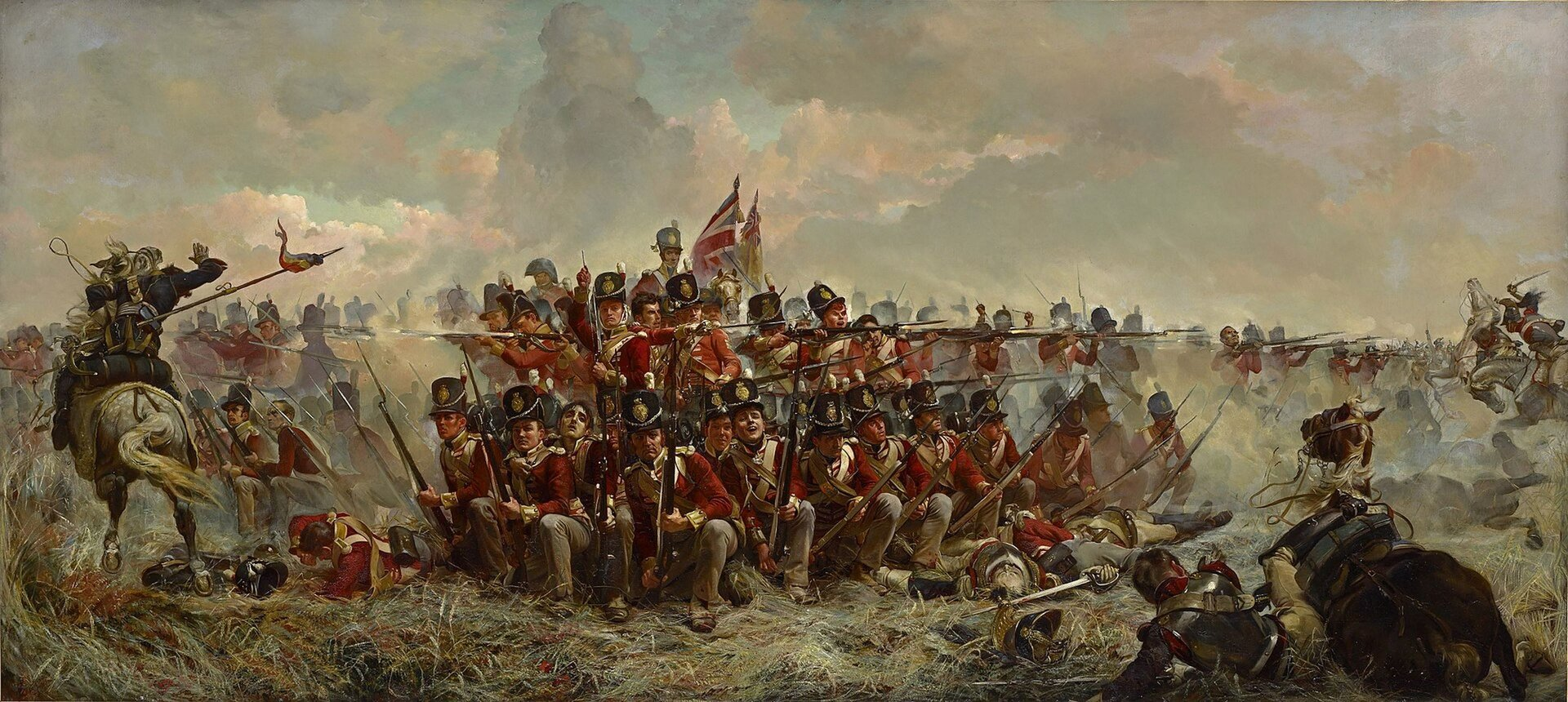 """Ilustracja interaktywna przedstawia dzieło Elizabeth Thompson """"28 Pułk pod Quarte Bras"""". Obraz ukazuje grupę żołnierzy. Mężczyźni trzymają karabiny zbagnetami nakierowane na przeciwnika. Ubrani są wczerwone mundury. Niektórzy patrzą wgórę, mają otwarte usta. Po lewej stronie konno galopuje żołnierz wgranatowym mundurze zwyciągniętą ręką. Wprawy, dolnym rogu znajduje się przewrócony koń zleżącym obok żołnierzem. Scena owita jest tumanami kurzu. Wtle obraz jest rozmyty, anad całością wisi ciężkie, zachmurzone niebo."""