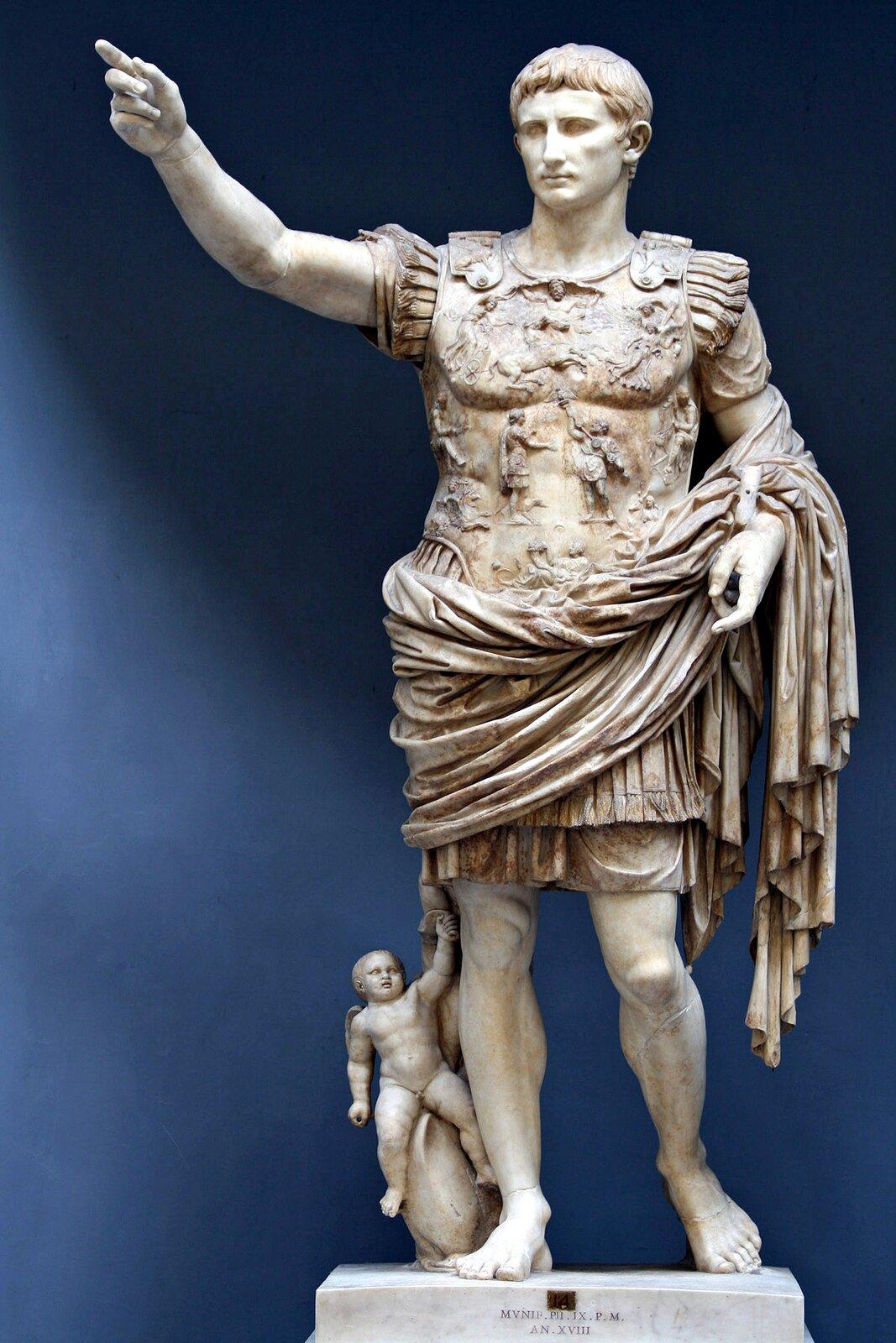 Zdjęcie przedstawia rzeźbę Gajusza Juliusza Cezara. Rzeźba wykonana zbiałego kamienia. Postać przodem do odbiorcy. Cezar wtradycyjnej zbroi rzymskiej. Tors iramiona zakryte zbroją. Lewa ręka uniesiona. Prawa ręka przytrzymuje togę zawiniętą wokół bioder. Głowa mała. Włosy krótkie. Grzywka równo przycięta nad brwiami. Nos iuszy małe. Twarz bez zarostu. Szyja szeroka. Nogi umięśnione. Stopy bez obuwia. Prawa noga lekko zgięta do tyłu, wsparta na palcach.