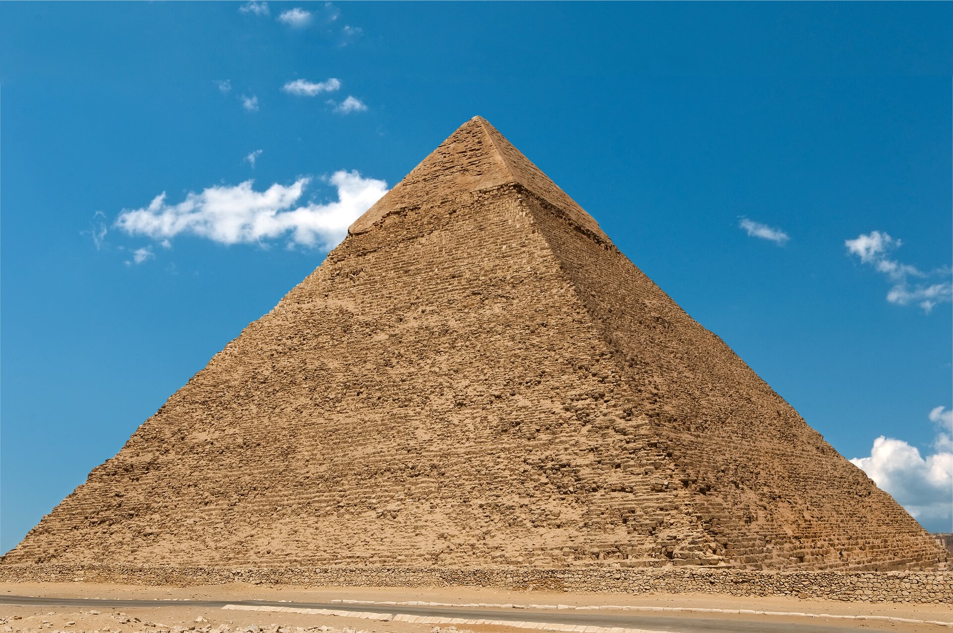 Ilustracja przedstawia piramidę Chefrena wGizie. Piramida ma kształt ostrosłupa opodstawie kwadratu. Jest wkolorze ciemnego piasku. Wtle niebieskie niebo zkilkoma małymi białymi chmurkami.
