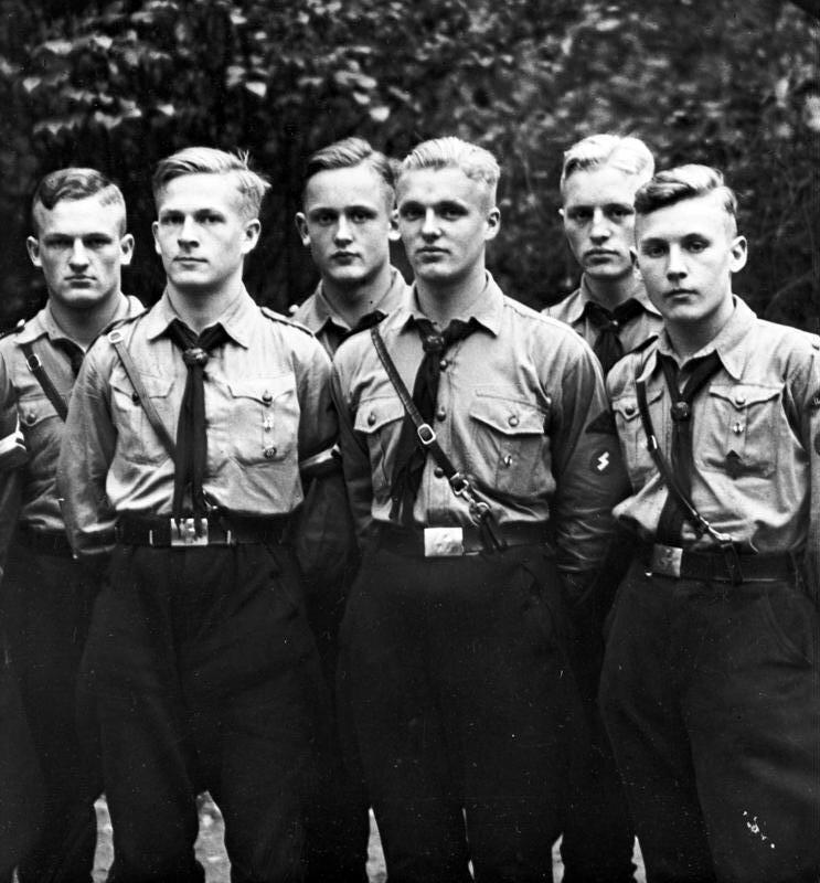 """Grupa Hitlerjugend """"Należymy do Hitlerjugend od dziesiątego roku życia. Spędzamy razem mnóstwo czasu: wszkole, na specjalnych zbiórkach po lekcjach iwniedziele, atakże na obozach podczas wakacji. Dużo przebywamy na świeżym powietrzu – staramy się być coraz sprawniejsi, bo to potrzebne, by wprzyszłości dobrze walczyć za ojczyznę. Chcemy być dobrymi Niemcami, dbać orozwój naszego państwa, zwalczać Żydów iinnych wrogów naszej aryjskiej rasy. Kierunek wytycza nam Adolf Hitler ijego partia – NSDAP"""". Źródło: Grupa Hitlerjugend, 1933, Bundesarchiv, licencja: CC BY-SA 3.0."""
