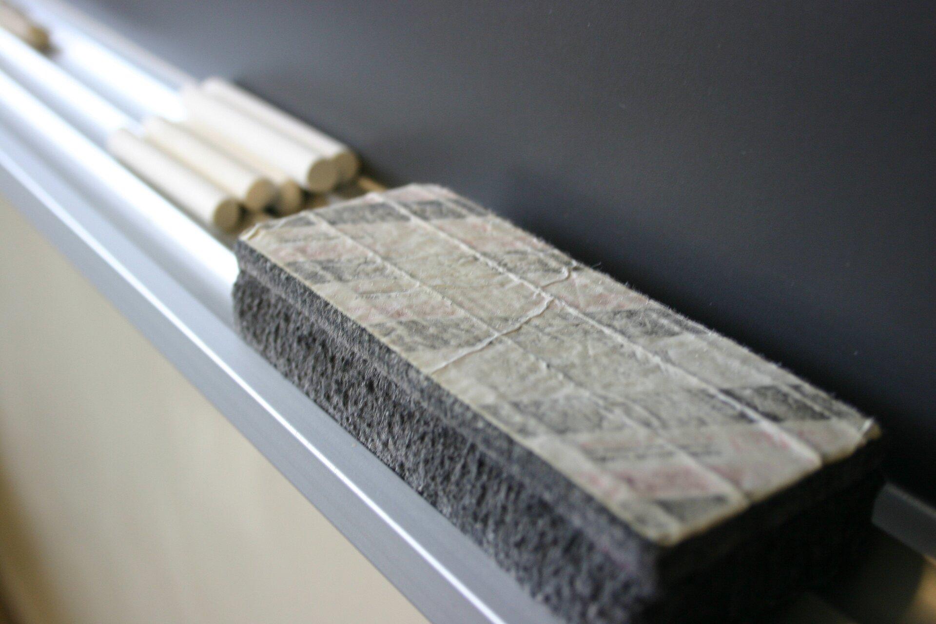 zdjęcie przedstawia gabkę do zmazywania tablicy szkolnej, wtle tablica