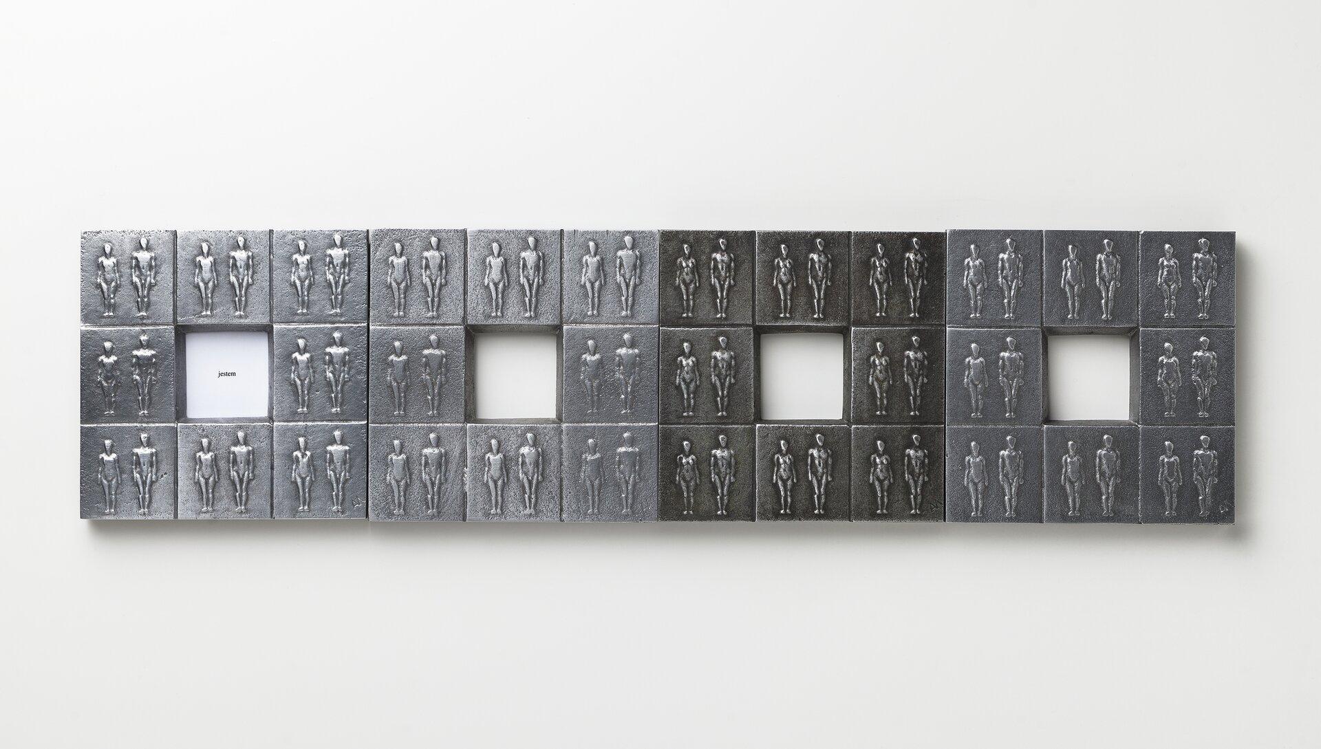 """Ilustracja przedstawia pracę Alicji Majewskiej """"Tożsamość"""". Jest to relief, składający się z32 metalowych płytek zwizerunkami tych samych, powtarzających się postaci. Praca podzielona jest na cztery kwadraty zczworokątnym otworem wśrodku. Wszystkie są zespolone wpoziomie."""
