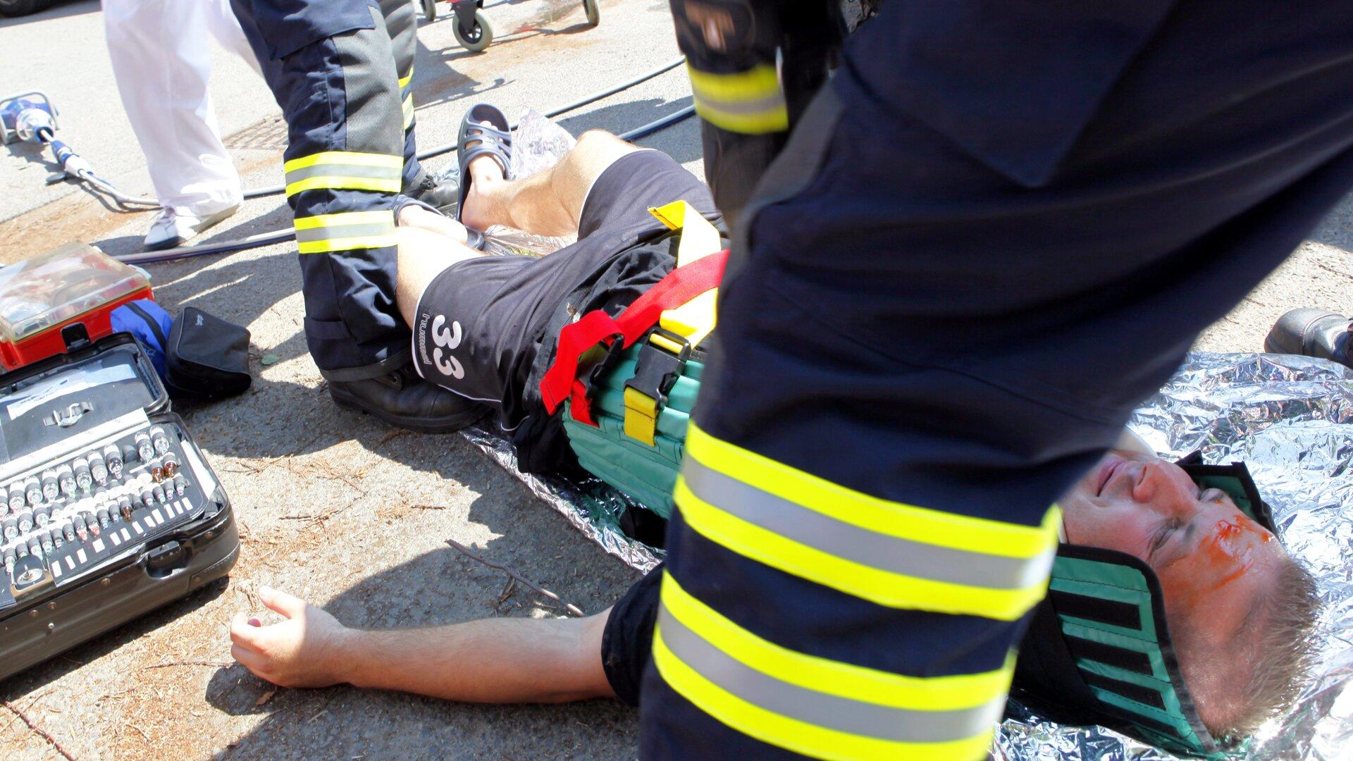Ilustracja przedstawia akcję ratowniczą. Mężczyzna leży na folii iprawdopodobnie jest ofiarą wypadku samochodowego. Założony ma kołnierz oraz inne elementy, zabezpieczające kręgosłup. Nad nim stoi dwóch strażaków. Wtle widać, że wakcji uczestniczy więcej osób.