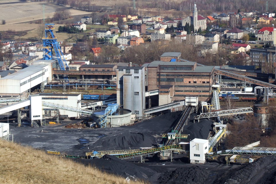 Fotografia prezentująca teren kopalni węgla kamiennego. Widoczne liczne zabudowania oraz hałdy węgła.