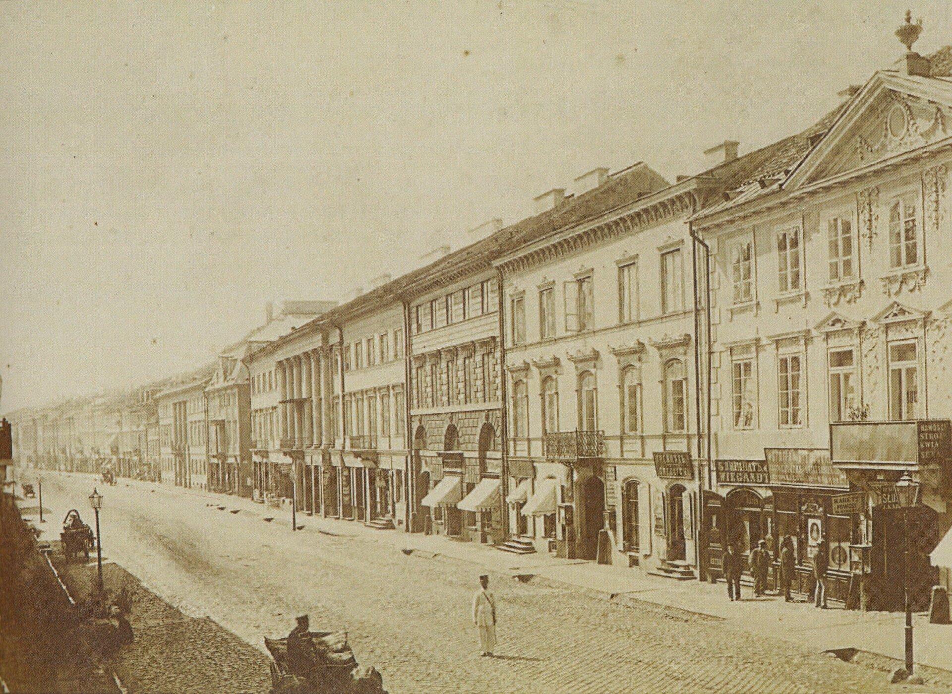 Ilustracja przedstawiająca XIX wieczną fotografię ulicy Nowy Świat wWarszawie. Jest to nowoczesna brukowana ulica zwysokimi kamieniczkami na dole których znajdują się liczne sklepy, kawiarnie .