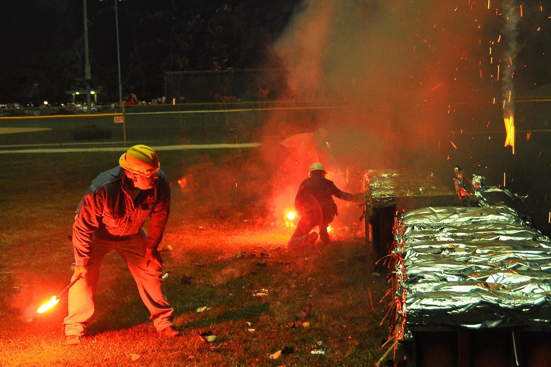 Zdjęcie przedstawia pracowników firmy pirotechnicznej przygotowujących profesjonalny pokaz sztucznych ogni. Obaj mają na sobie ubrania ochronne, kaski itrzymają wrękach zapalone flary, które posłużą im do podpalenia lontów.
