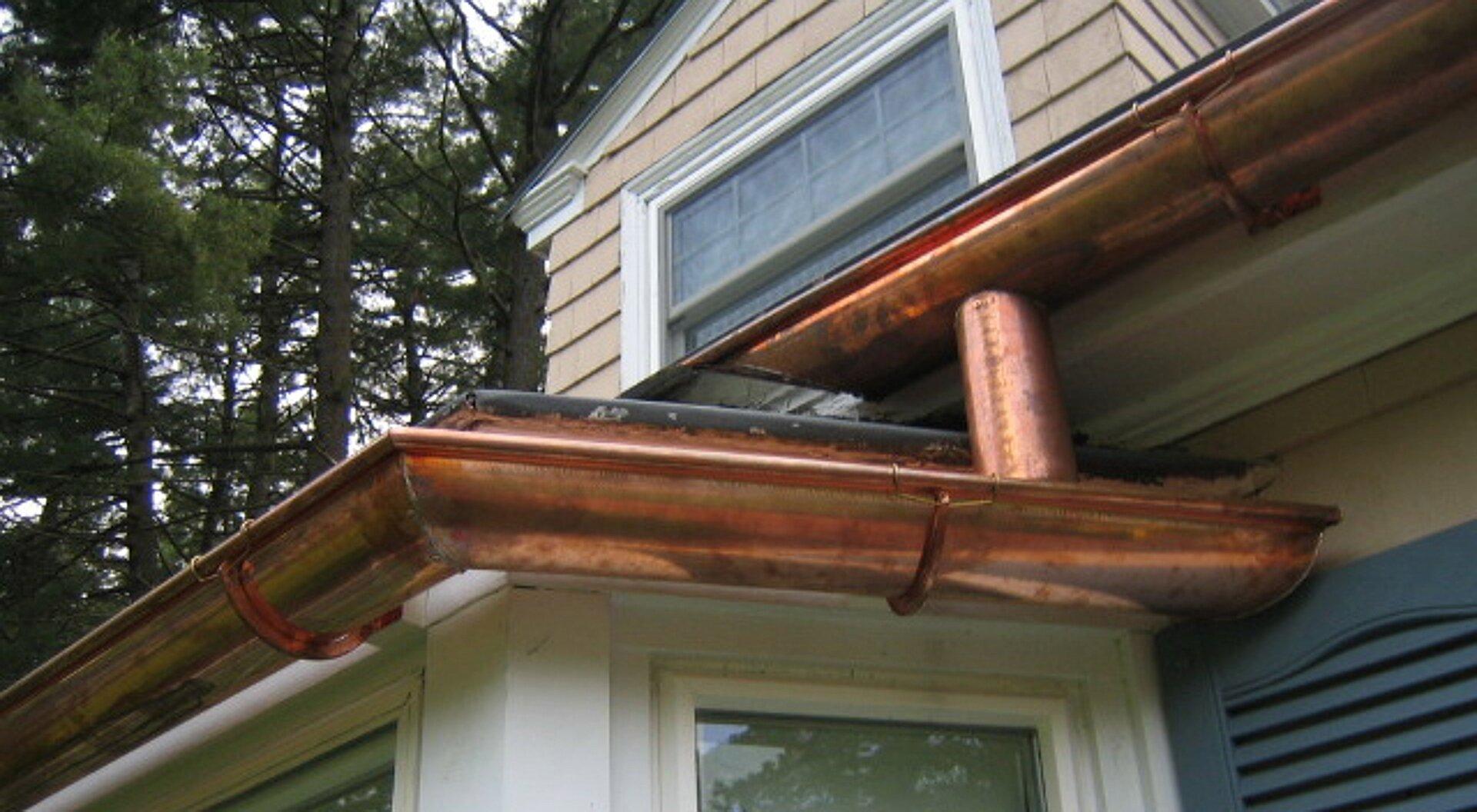 Zdjęcie przedstawia zbliżenie miedzianych rynien na dachu domu.