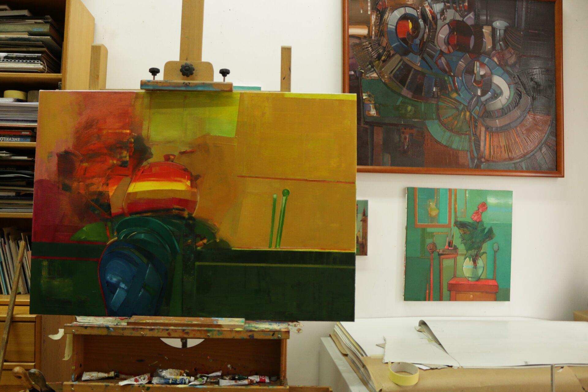 Ilustracja przedstawia fragment wnętrza pracowni malarskiej. Wcentrum kadru znajduje się sztaluga zabstrakcyjnym obrazem olejnym wżółto-czerwono-zielonej tonacji. Za nim ustawiony jest wysoki regał zksiążkami. Po prawej stronie stoi niska biała szafka zleżącą na niej szarą teczką zrysunkami. Na białych ścianach pomieszczenia wiszą kolorowe obrazy.