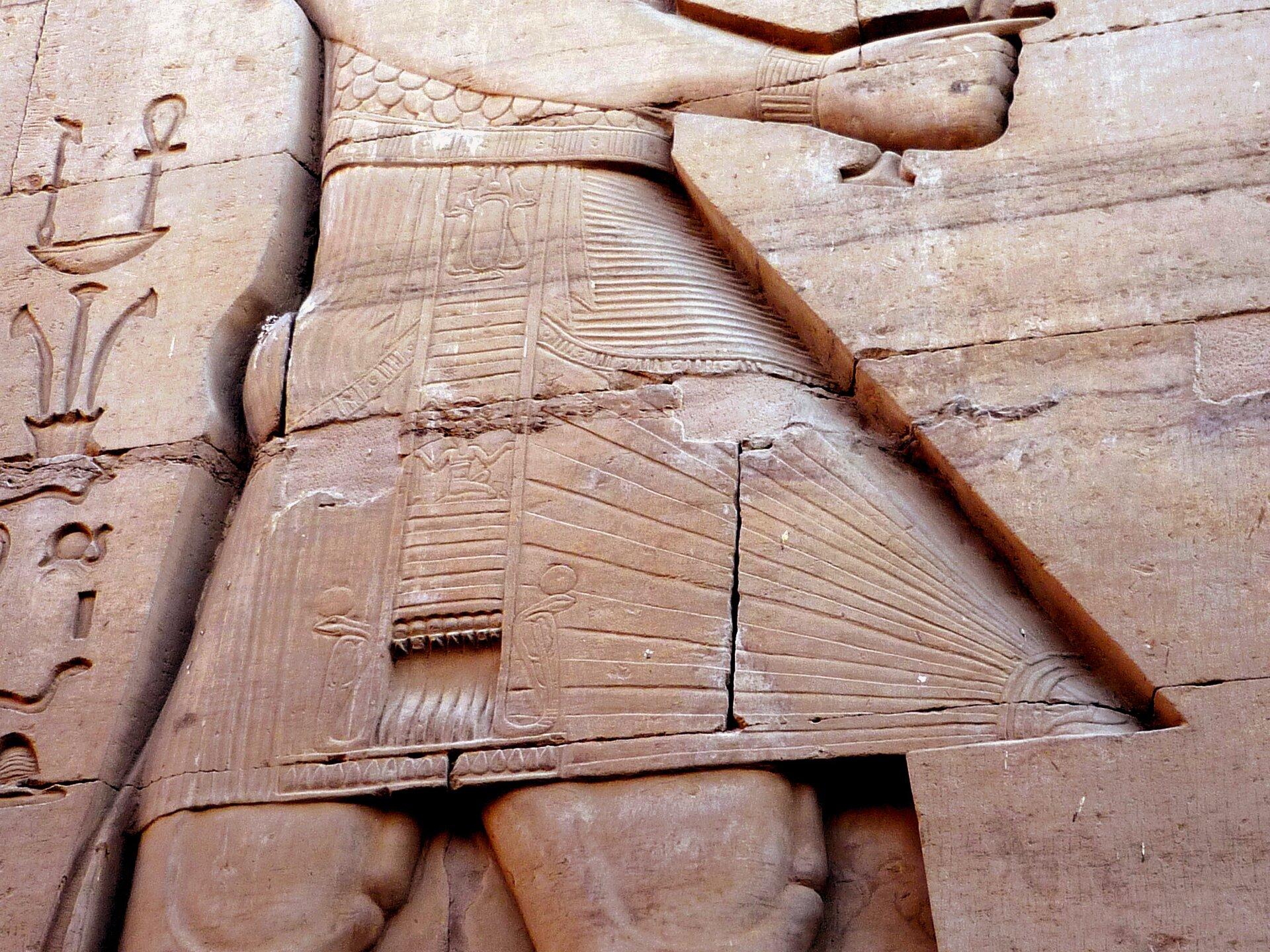 Ilustracja przedstawia Relief wklęsły ze ściany świątyni wKom Obo wEgipcie. Na fotografii widać fragment rzeźby, na którym widnieje część starożytnego stroju. Na stroju widoczne są promienie słoneczne oraz poziome kreski. Obok stroju widnieje pismo naścienne.