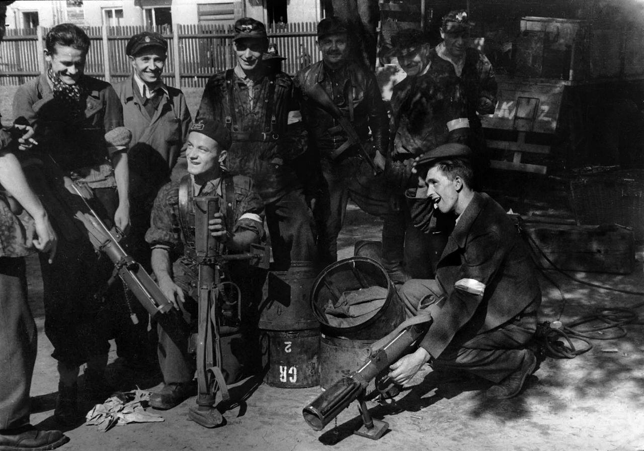 Grupa uśmiechniętych żołnierzy wmundurach iwubraniach cywilnych izopaskami na ramionach pozuje do zdjęcia na ulicy, pod drzewem. Żołnierze trzymają wrękach broń.