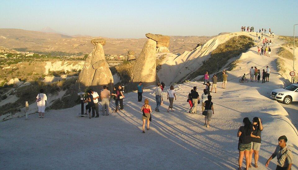 Na zdjęciu turyści na płaskim szczycie wzniesienia. Na skraju teleskopy. Woddali ostańce wkształcie grzybów. Wtle rozległe tereny górskie.