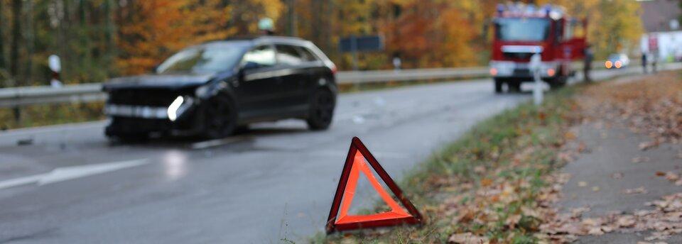 Kolorowe zdjęcie przedstawia sytuację po wypadku na drodze. Nawierzchnia jezdni jest mokra, wtle widać drzewa zżółto-pomarańczowymi liśćmi. Na pierwszym planie zdjęcia trójkąt ostrzegawczy – stoi na poboczu drogi, na trawie imokrych brązowych liściach. Trójkąt ostrzegawczy składa się zdwóch trójkątów – na zewnątrz ciemnoczerwonego, wewnątrz – jaskrawopomarańczowego. Środek trójkąta jest pusty. Za trójkątem, po lewej stronie jezdni, stoi czarny samochód, który uległ wypadkowi. Przód samochodu jest stłuczony, przednia klapa lekko uniesiona do góry, zderzak obniżony, lewa lampa wsamochodzie pali się jasnym światłem, na jezdni przed autem leżą drobne części, które odpadły podczas zderzenia. Zprzodu, przed samochodem, na jezdni namalowana jest duża biała strzałka informująca okonieczności zjechania zlewego na prawy pas jezdni. Ztyłu, za czarnym samochodem, na prawym pasie jezdni, stoi wóz strażacki. Obok niego stoi mężczyzna. Ztyłu woddali, za wozem strażackim, na lewym pasie jezdni, stoi jasny samochód osobowy zwłączonymi przednimi lampami.
