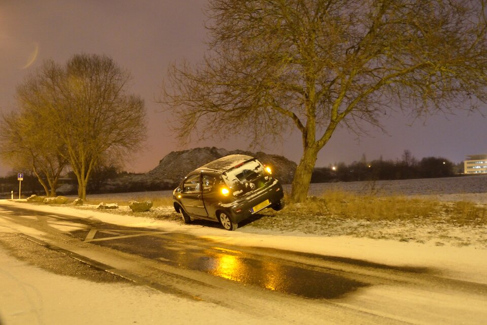 Zdjęcie przedstawia skutki gołoledzi. Widać samochód leżący wrowie. Jezdnia pokryta śniegiem ilodem.