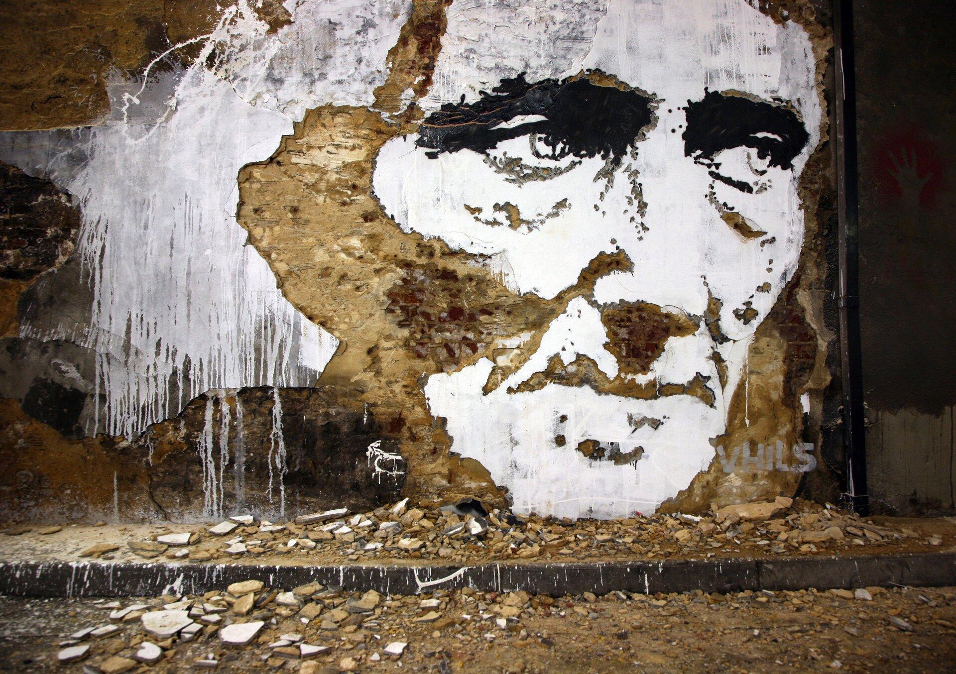 Ilustracja przedstawia portret mężczyzny wykonany techniką scratchingu, wykonany przez Alexandre'a Farta. Ukazuje twarz, której cienie wydrapano wtynku, ana pozostawionych fragmentach naniesiono białą farbę. Pod ścianą leżą fragmenty zdrapanego tynku.