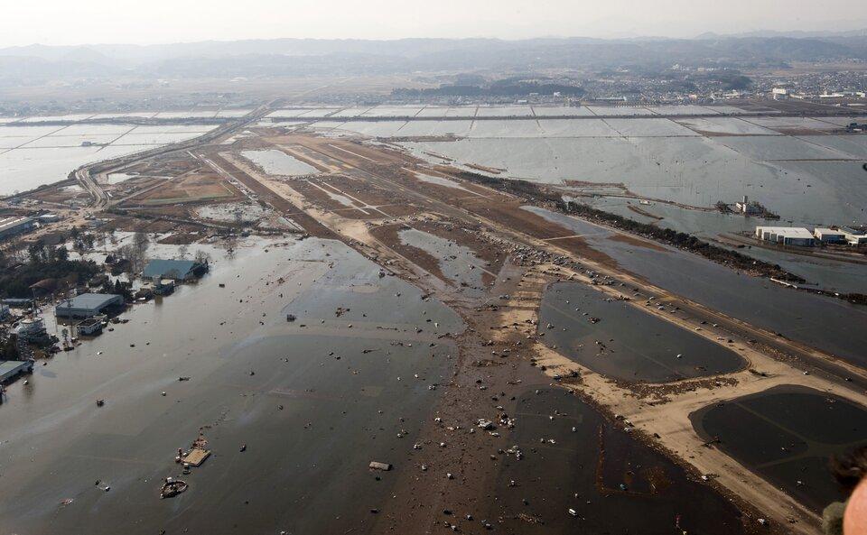 Na zdjęciu zalane lotnisko, pasy startowe pod wodą, zniszczone zabudowania.