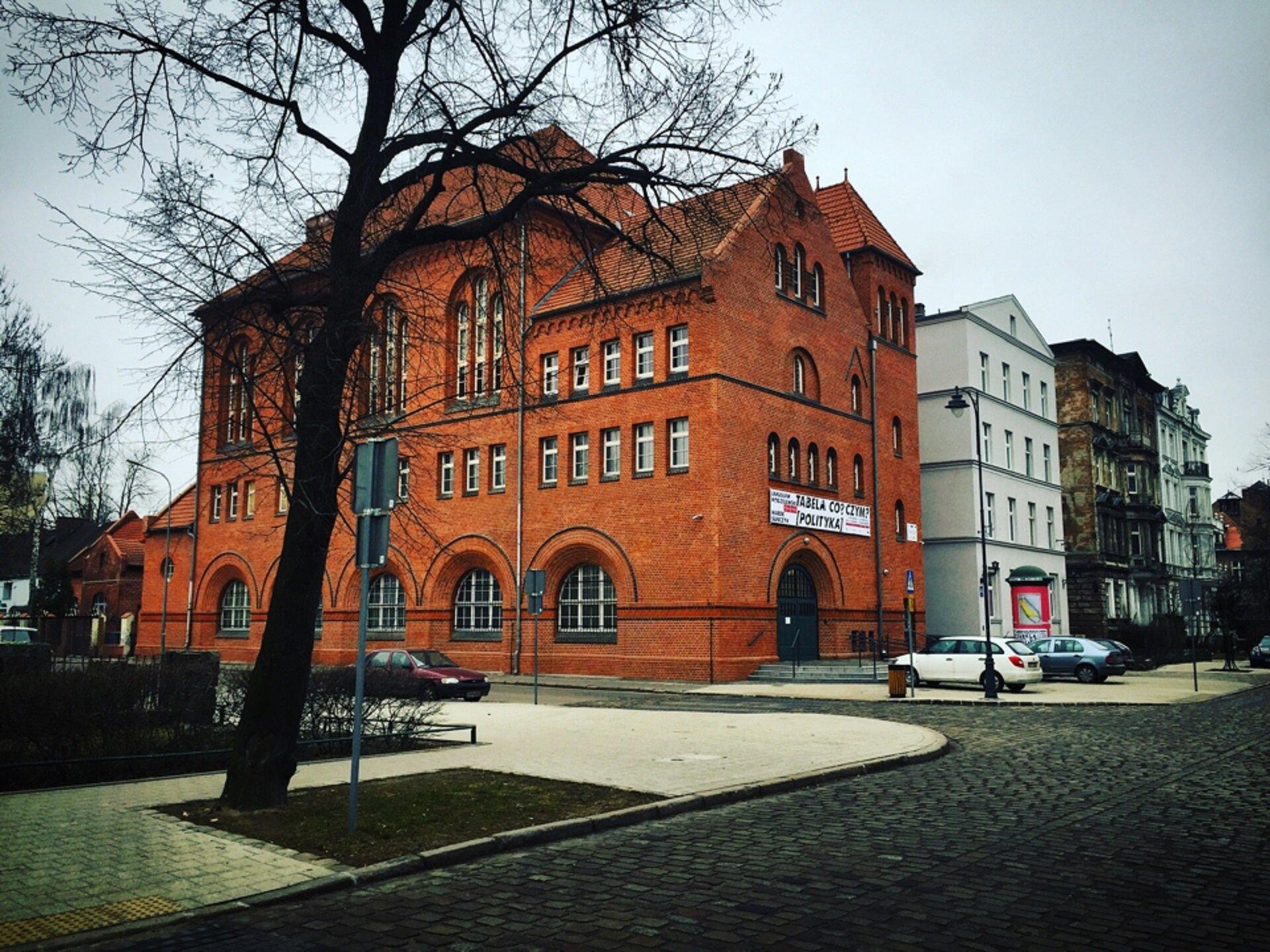 Ilustracja przedstawia CSW Łaźnię wGdańsku - widok zzewnątrz. Budynek jest wykonany zczerwonej cegły. Ma on dwuspadowy dach. Jest zbudowany zkilku kondygnacji. Okna znajdujące na ścianach różnią się od siebie. Część znich jest klasycznymi prostokątnymi oknami, druga część okien jest dużo większa izwieńczona półkolem przy górnej części. Do budowli przylegają inne budynki.