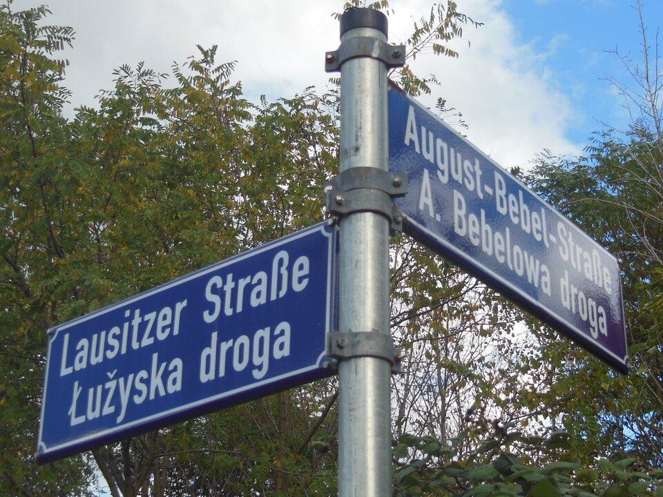 Na zdjęciu słup uliczny znazwami ulic. Niebieskie tabliczki, białe napisy – niemieckie iłużyckie nazwy ulic.