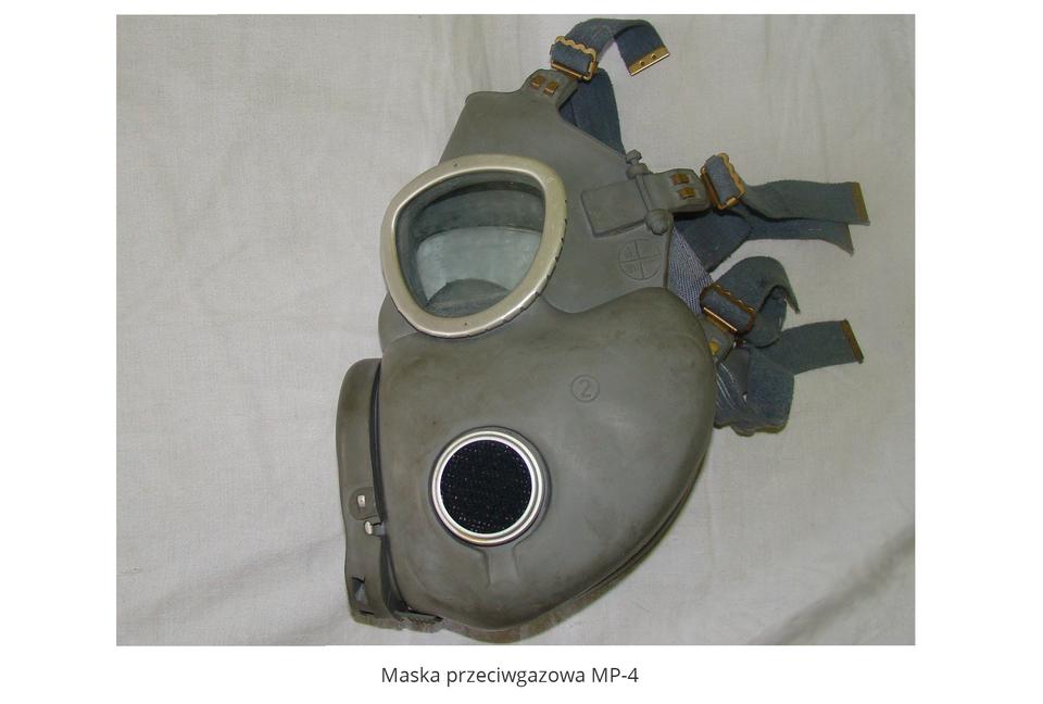 Zdjęcie przedstawia gumową maskę przeciwgazową typu MP-4. Maska ciemnozielona, jej część twarzowa ma dwa otwory do patrzenia ze szkła. Zprzodu maski wystający element zawierający wlot powietrza. Część policzkowa wypukła, zawiera wkładkę zpochłaniaczem . Część twarzowa zakończona paskami zmetalowymi sprzączkami.